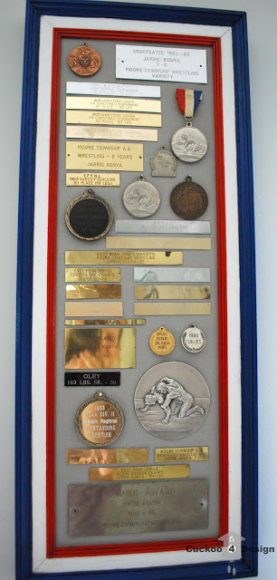 putting vintage metals and plaques on display in an old painted frame
