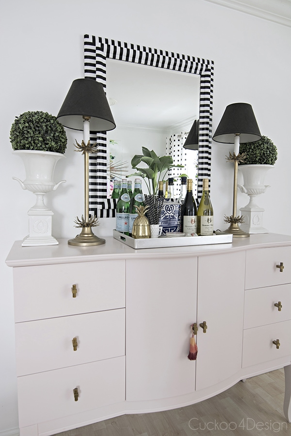 pink dining room buffet with black and white striped mirror
