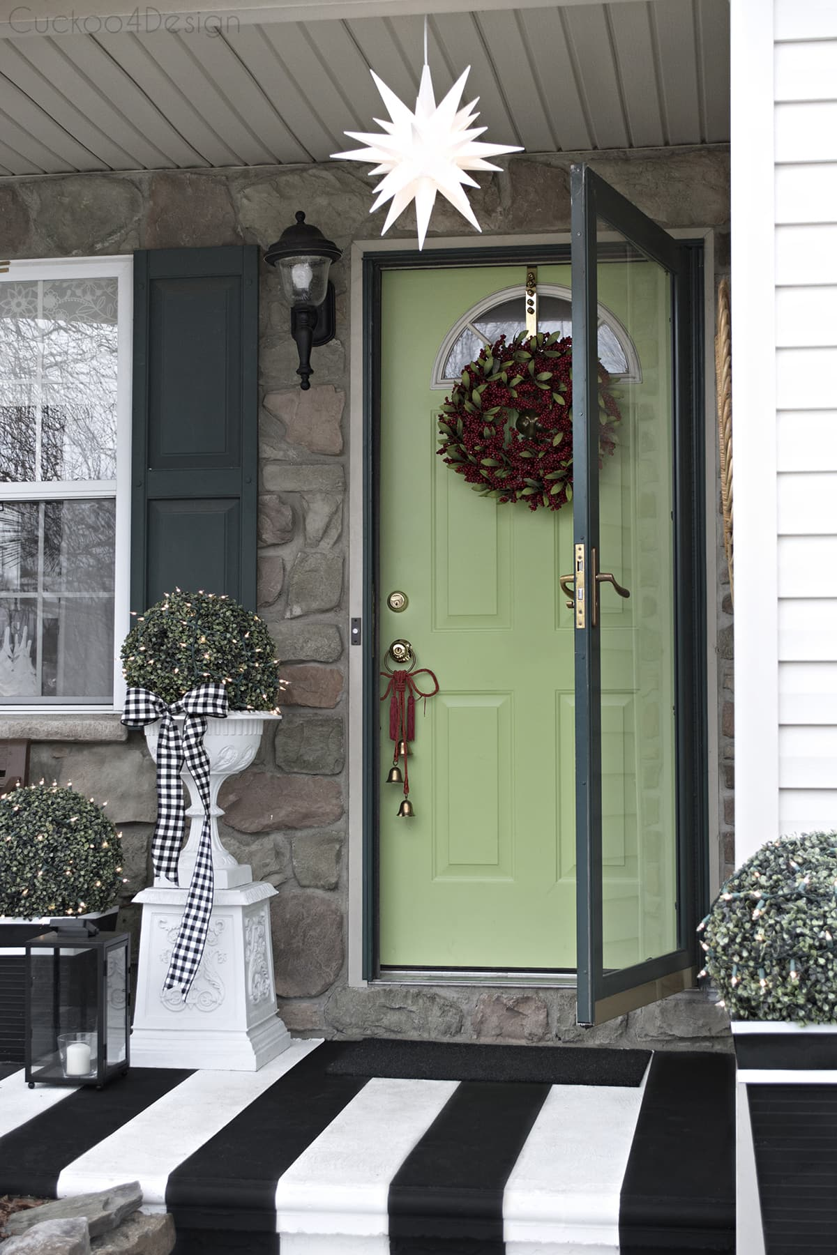 black and white striped porch with lime green door and red wreath