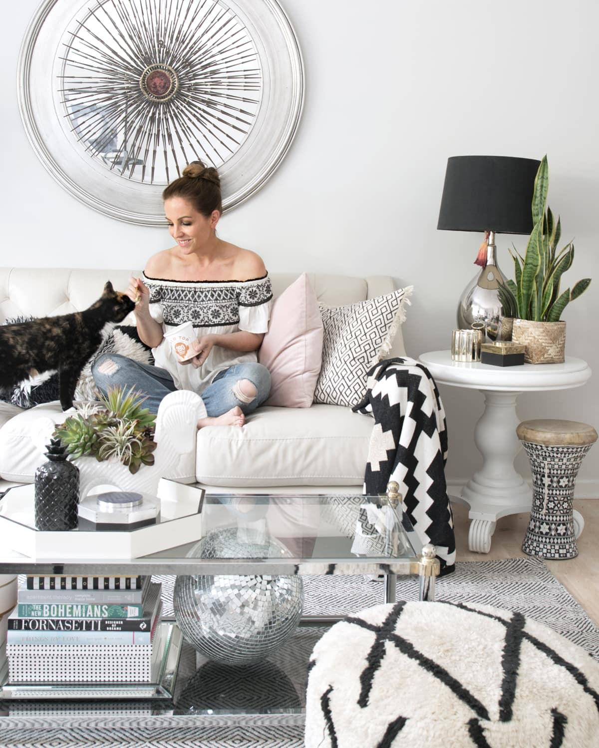 neutral eclectic living room with blush accents and lots of black and white decor