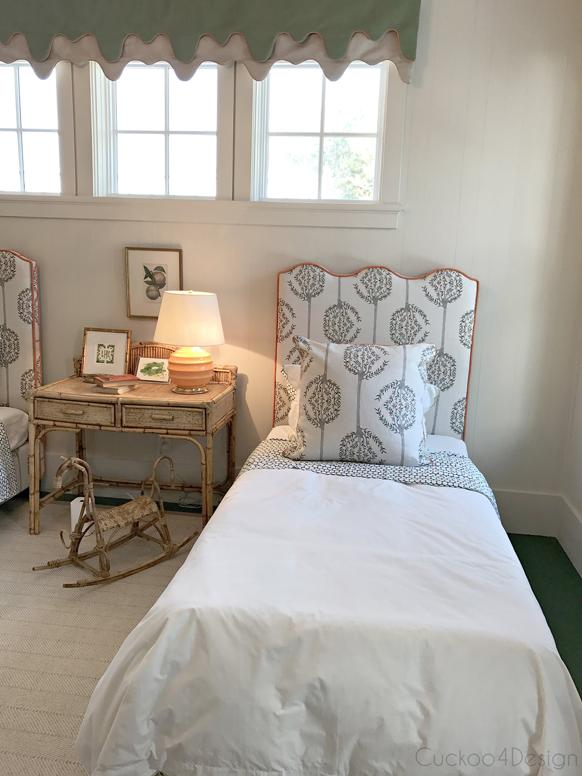 kids bedroom with upholstered headboard, orange trim and vintage wicker furniture