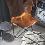 leather butterfly chair with dark green walls